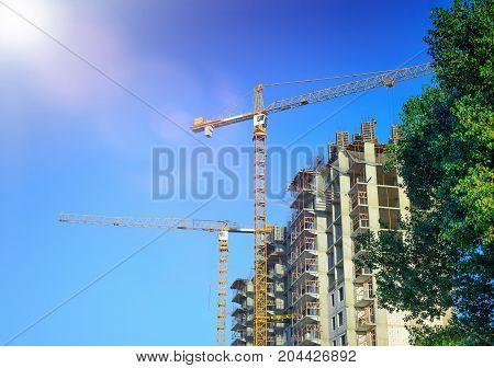 Crane and workers at construction of residental building against blue sky in sunny day