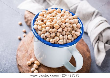 Raw uncooked organic chickpeas in white enamel mug on rustic wooden board on light gray stone background. Healthy vegan vegetarian food concept