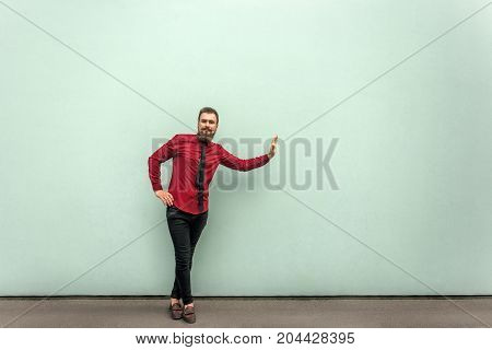 Business Person In Red Shirt, Tie And Black Casual Trousers, Standing On Gray Wall And Prop Somethin