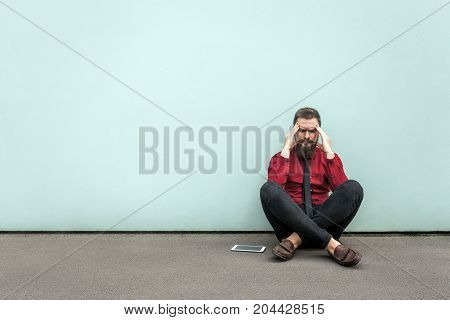 Young Adult Bearded Businessman Sits On The Ground.