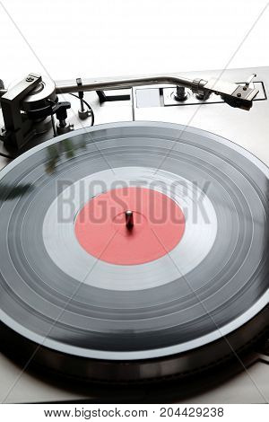 Vintage turntable in silver case with buttons and knobs on control panel with vinyl record with red label isolated on white background. top view closeup