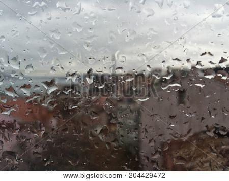 Rain Drops On Window Against Buildings