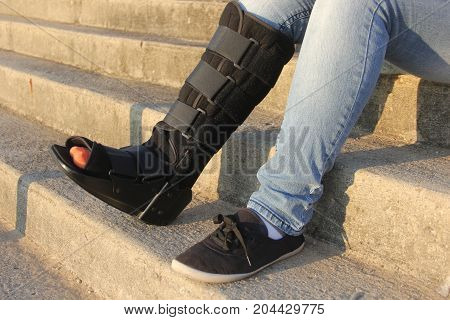 Woman with a walking cast boot on steps