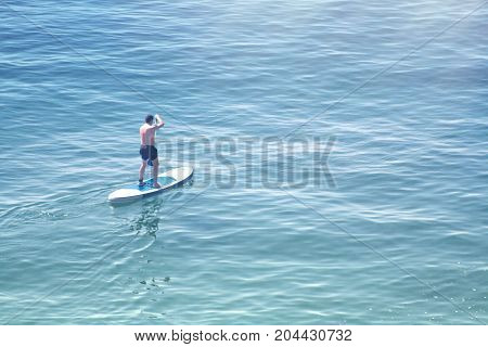 a man swims in the Board moving through the water using paddles in the open sea