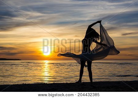 Silhouette Of Slim Woman Dancing With Scarf On The Beach