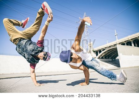 Two bbys doing some stunts - Street artist breakdancer taking an acrobatic selfie outdoors