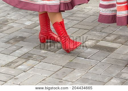 Woman wearing red high heels boots stage. Woman foot takes a step on the street. Women legs and feet with boots in close-up.