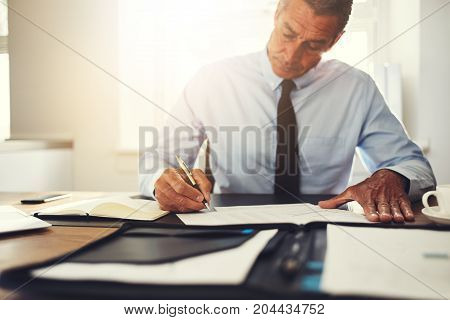 Businessman Sitting At His Office Desk Signing Documents