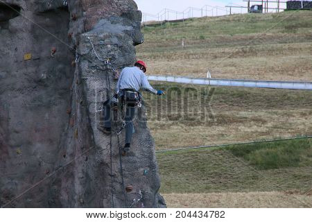 MAGDEBURG, GERMANY - September 16, 2017: A man practicing mountaineering at a climbing tower in Magdeburg.