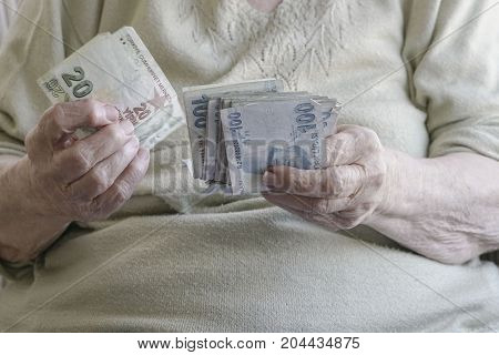 closeup wrinkled hands of senior woman counting money (turkish lira)