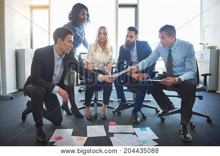 Focused Executives Discussing Paperwork Together In An Office