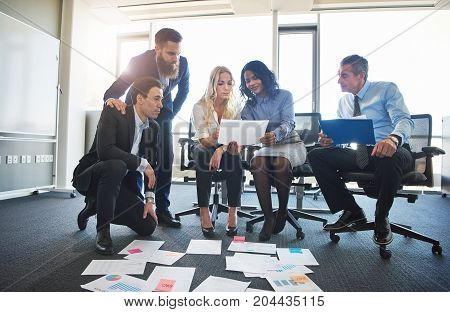 Focused Colleagues Discussing Paperwork Together In An Office