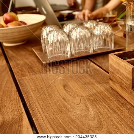 Closeup of brown wooden table in modern coffee shop. Toned image with a square ratio