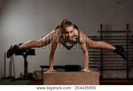 Athletic flexible girl doing exercises with wood box