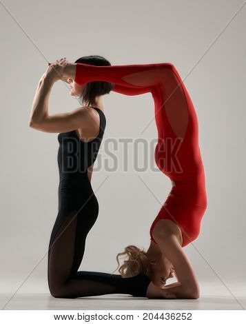 Portrait of two sporty woman doing acrobatic exercise