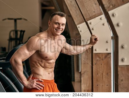 Portrait of happy smiling sporty man posing in fitness club