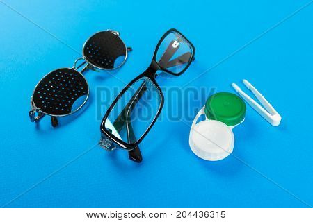 Pinhole glasses lenses with container and glasses for sight. Medical concept. A set of accessories for sight. Top view.