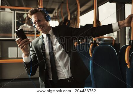 Smiling Businessman Standing On A Bus Listening To Music