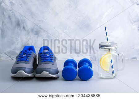 Sport composition with gray sneakers with blue shoelaces blue dumbbells mason jar with water lemon and blue straws on gray concrete background. Concept healthy lifestyle detox diet sport.