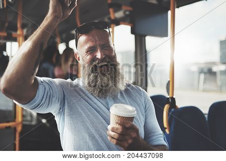 Mature man with a long beard laughing and drinking a takeaway cupe of coffee while standing on a bus during his morning commute