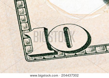 Detail of 10 dollars banknote isolated on white background. Stacked photo.