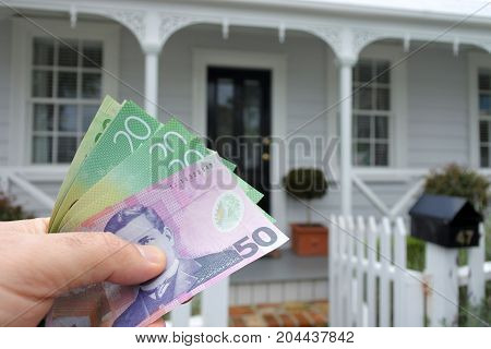A Mans Hand Holds Nz Dollar Bills Against A Front Of North American Hous