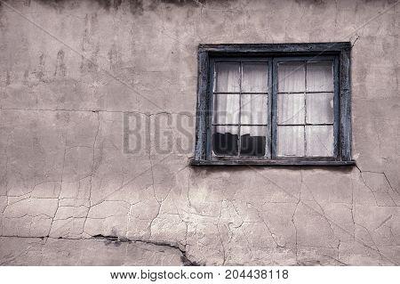 Rustic wood framed window in an old adobe wall