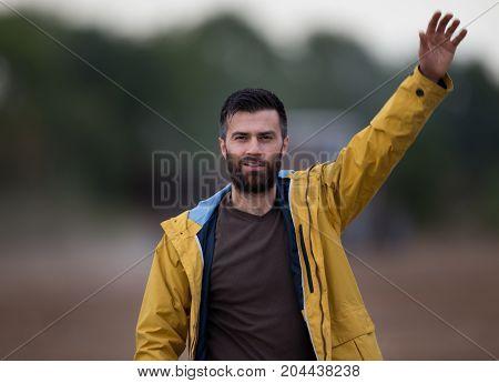 Man With Beard Waving Hand In Field