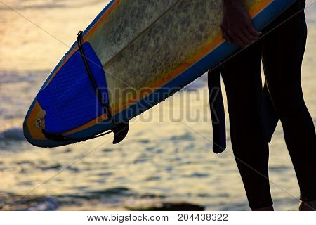 Detail of man seen from behind holding his surfboard in front of the sea during the sunset