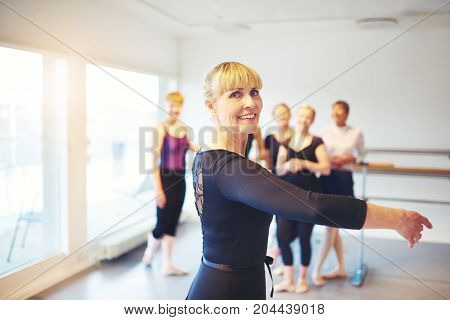 Active senior woman doing ballet in a dance studio with a group of friends in the background