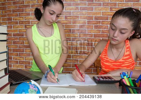 Two Young Girls studying on desk at home. Thoughts education creativity concept