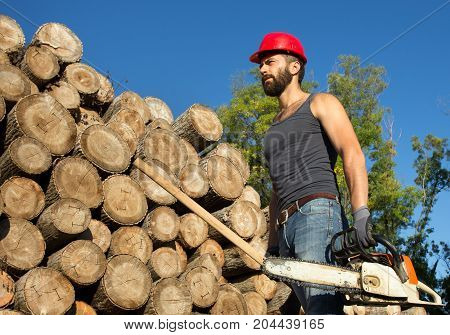 Lumberjack With Chainsaw And Ax In Forest