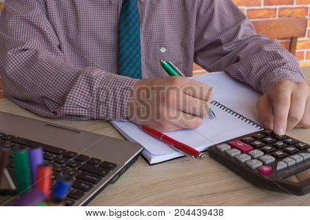 Man hand using calculator and writing make note with calculate about cost at home office. The Man and computer are using a calculator on the table in the office room