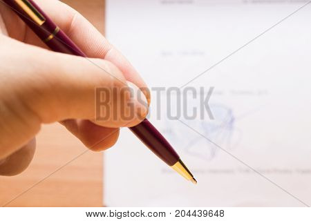 The hand holds a solid writing pen on the background of a document with a seal and a signature