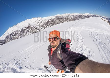Adult Alpin Skier With Beard, Sunglasses And Hat, Taking Selfie On Snowy Slope In The Beautiful Ital