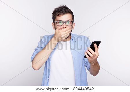 Emotional bearded guy holding his hand on cheek looking with eyes popped out and opened mouth into camera being shocked getting news about hurricane. Young man with scary look posing in white studio.