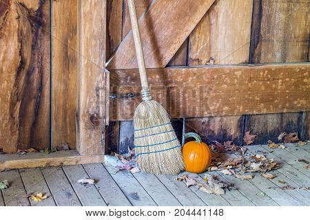 Straw Broom And Pumpkin In Rustic Wooden Old Barn Or Shed
