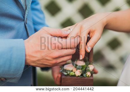 Newlyweds exchange rings, groom puts the ring on the bride's hand. wedding ceremony