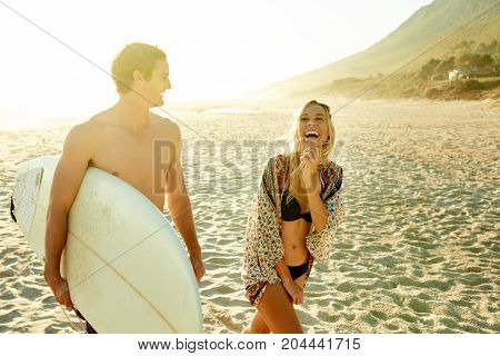 Young Couple Laughing And Walking Along The Beach With Surfboard