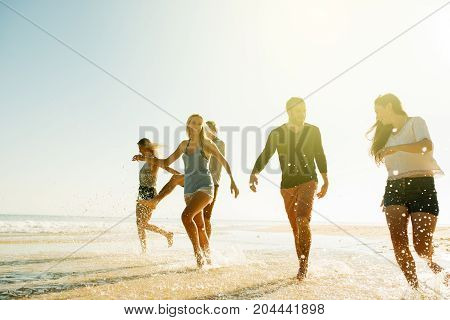 Young Friends Splashing Through Water While Walking At The Beach