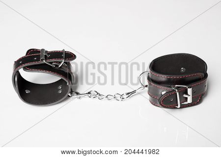 Black Leather Handcuffs On White Background. Sex Toy.