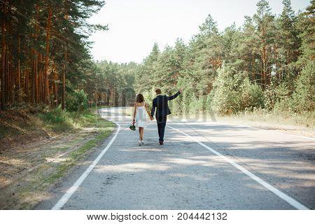 Newlyweds Go On The Road. Wedding Walk.