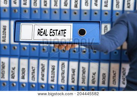 Real Estate concept. Young man holding ring binder.