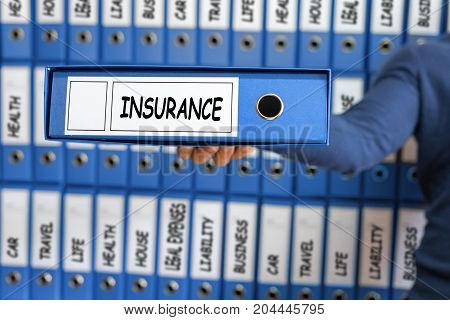 Insurance concept risk management. Young man holding ring binder.