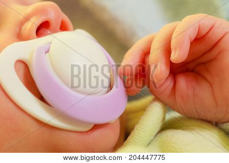 Infant care beauty of childhood concept. Little newborn baby sleeping calmly in bed with teat in mouth.