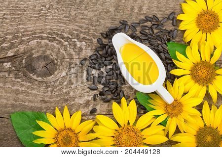 Sunflower oil, seeds and flower on wooden background with copy space for your text. Top view.