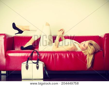 Fashion clothes clothing accessories trendy outfits concept. Woman wearing light outfit and black high heels lying on red sofa presenting white bag