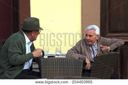 Ronda, Spain - May 3, 2014: Elderly men talking in the street cafe in Ronda, Spain