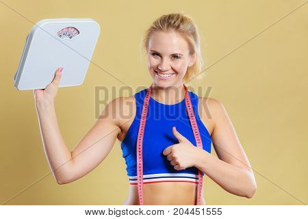 Fit fitness woman with scale happy blonde girl holding weight scales showing thumb up gesture sign. Slimming diet and healthy lifestyles concept