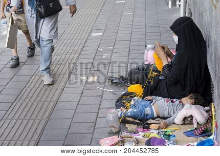 Tehran IRAN - September 3 2017 Street photography muslim woman weave loofah with yellow yarn in pavement. little girl slept beside her.
